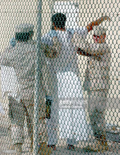 Guards search a detainee at the Camp Delta detention facility at Guantanamo Bay Cuba Tuesday June 13 2006 Three detainees at the camp were found dead...