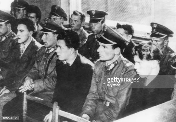 Guards sitting in a courtroom with some of the youths accused of storming the prison and a militia post during an antiCommunist uprising in Poznan...