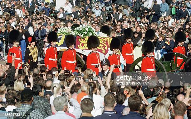 Guardsmen escort the coffin of Diana Princess of Wales draped in the Royal Standard as the cortege passes through crowds gathered outside Buckingham...