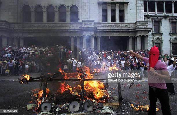 Estudiantes de la estatal Universidad de San Carlos simulan la quema de una tanqueta frente al Palacio Nacional de la Cultura en la conmemoracion del...