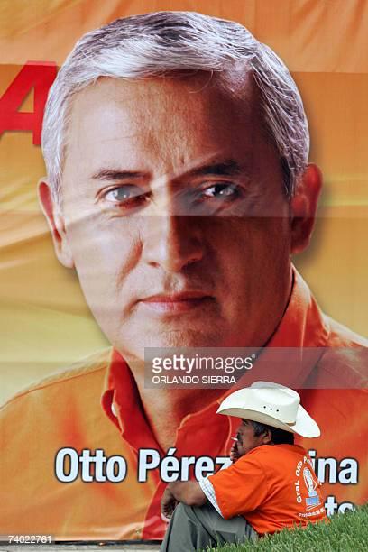 Un hombre fuma sentado frente a propaganda del general retirado Otto Perez Molina candidato a la presidencia de Guatemala por el Partido Patriota en...