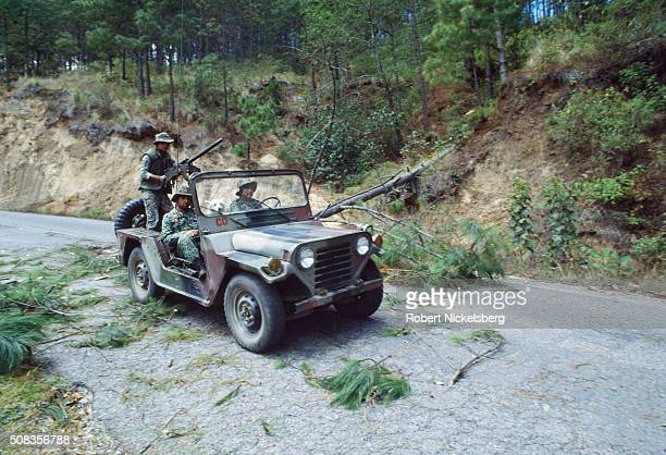 Guatemalan Army soldiers drive a jeep past a section of the Pan American Highway previously blocked by felled trees during the ongoing civil war Los...