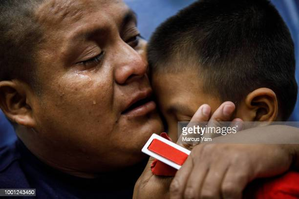 Guatemalan asylum seeker Hermelindo Che Coc cries as he reunites with his 6yrold son Jefferson Che Pop in the Los Angeles area on July 14 2018 The...