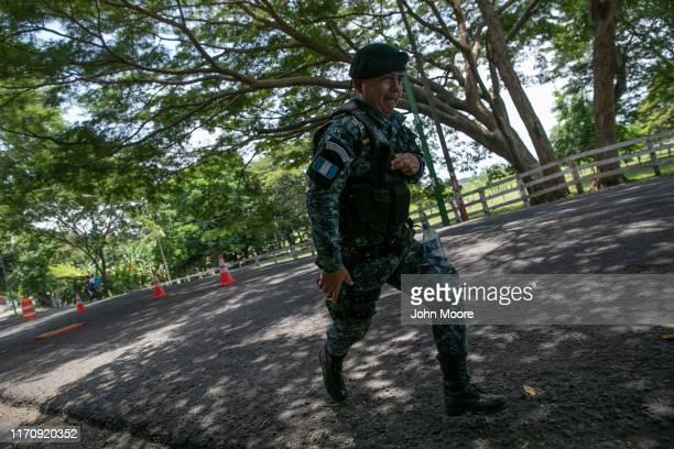 Guatemalan border policeman runs while manning a checkpoint with U.S. Advisors on August 28, 2019 in Ciudad Pedro de Alvarado, Guatemala, near the...