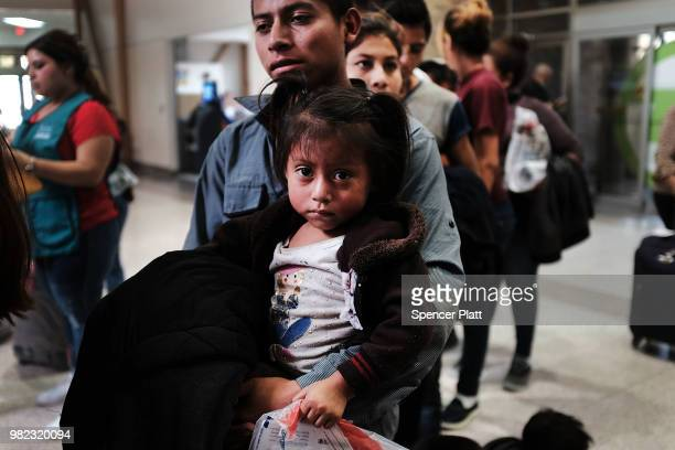 Guatemalan father and his daughter arrives with dozens of other women men and their children at a bus station following release from Customs and...