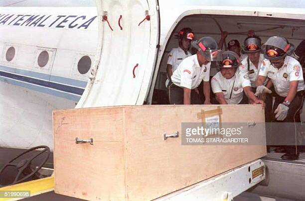 Guatemalan firemen load caskets into a Guatemalan air force plane containing the remains of victims of the Aviateca flight 901 at the Comalapa...