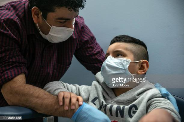 Guatemalan immigrant Marvin comforts his son Junior after a nurse drew blood for a COVID19 antibody test at a clinic on May 5 2020 in Stamford...