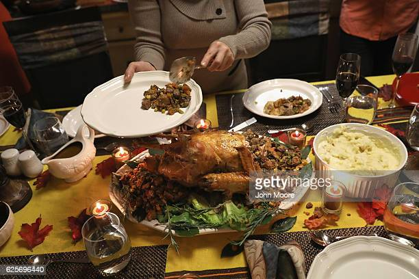 Guatemalan immigrant serves stuffing from the Thanksgiving turkey on November 24 2016 in Stamford Connecticut Family and friends some of them US...