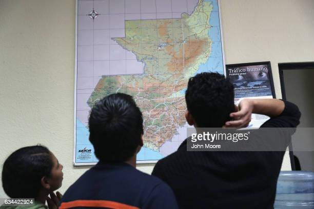 Guatemalan immigrants look over a map of their country after arriving on an ICE deportation flight on February 9 2017 to Guatemala City Guatemala The...