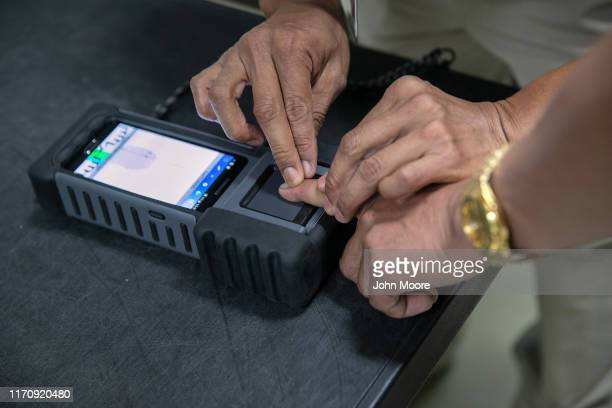 Guatemalan immigration agent fingerprints a traveler during a secondary screening while being instructed by an American Department of Homeland...