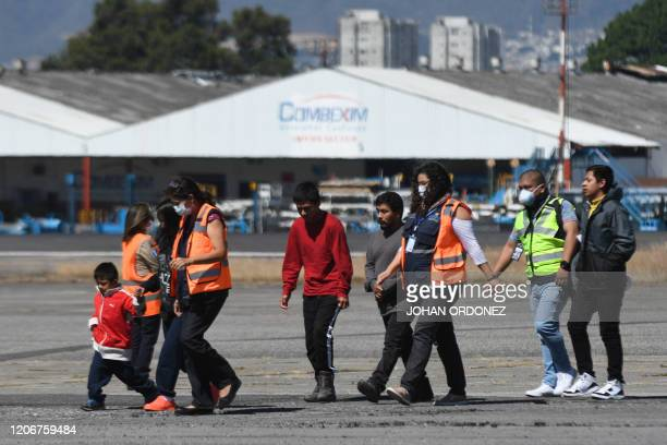 Guatemalan immigration officials use protective equipment as a preventive measure against the new coronavirus, COVID-19, as they receiving Guatemalan...
