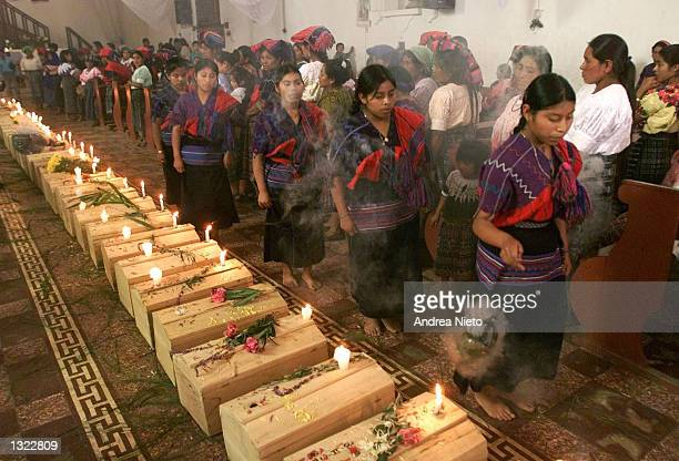 Guatemalan Mayan Quiche Indian women dance and burn incense around 41 coffins of victims found in a 1980''s clandestine cemetery during mass July 5...