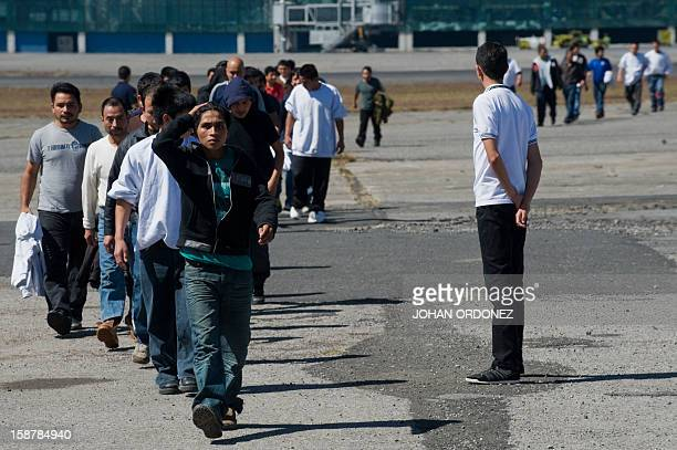 Guatemalan migrants deported from different parts of the US walk after disembarking from a plane in Guatemala City on December 28 2012 Officials from...