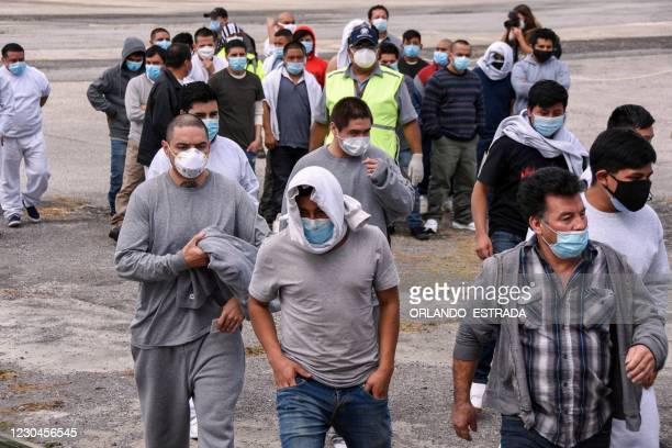 Guatemalan migrants deported from the United States, walk upon their arrival at the Air Force Base in Guatemala City on January 6, 2021. - During...