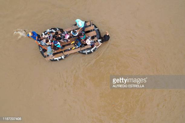 TOPSHOT Guatemalan migrants use a makeshift raft to illegaly cross the Suchiate river from Tecun Uman in Guatemala to Ciudad Hidalgo in Chiapas State...