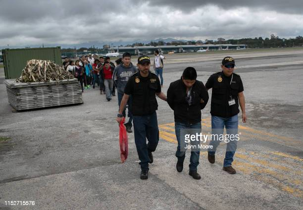Guatemalan police escort an accused criminal on the airport tarmac after he and other Guatemalans were deported from the United States on May 30,...