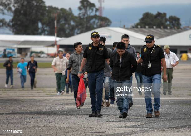 Guatemalan police escort an accused criminal on the airport tarmac after he and other Guatemalans were deported from the United States on May 30 2019...