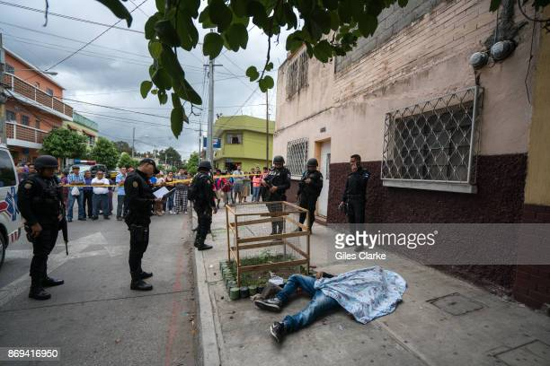 Guatemalan police inspect a victim of gang violence in the busy suburb of Zone 18 on October 21 2017 in Guatemala City Guatemala Photo by