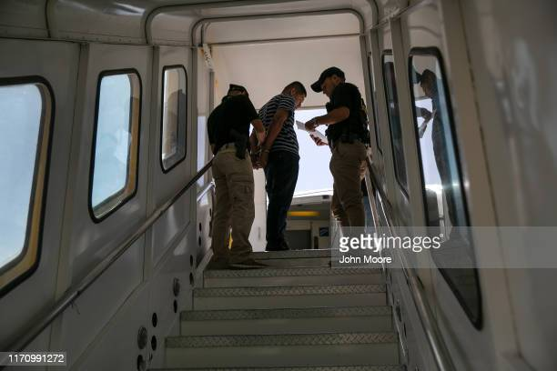 Guatemalan police prepare to escort a convicted criminal who arrived on an ICE deportation flight from Brownsville, Texas on August 29, 2019 to...