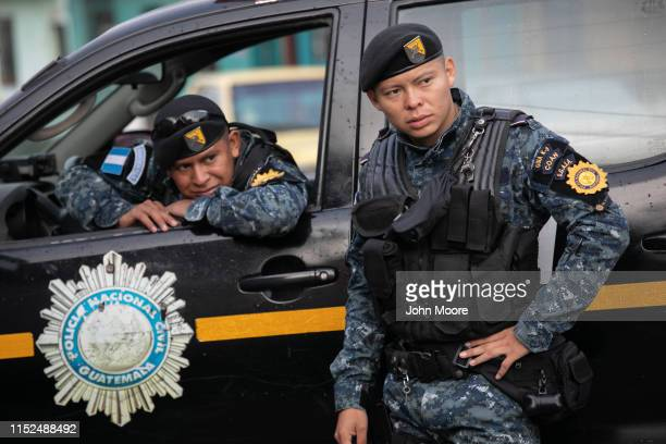 Guatemalan police stand at the the scene of a raid where a suspected human trafficker was taken into custody on May 29 2019 in Guatemala City US...
