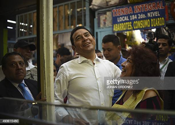 Guatemalan presidential candidate for the National Front of Convergence party Jimmy Morales greets supporters during a visit in Central market in...