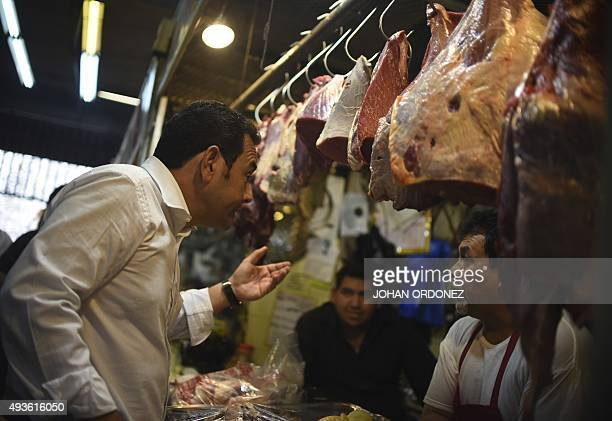 Guatemalan presidential candidate for the National Front of Convergence party Jimmy Morales speaks with a butcher during a visit to the Central...