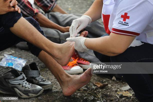 Guatemalan Red Cross medics treat members of a migrant caravan on October 16, 2018 near Quezaltepeque, Guatemala. The caravan of more than 1,500...