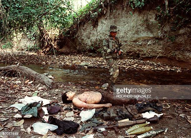 Guatemalan soldier walks past the body of a guerrilla killed 20 February 1992 in one of two clashes in southern Guatemala with members of the...