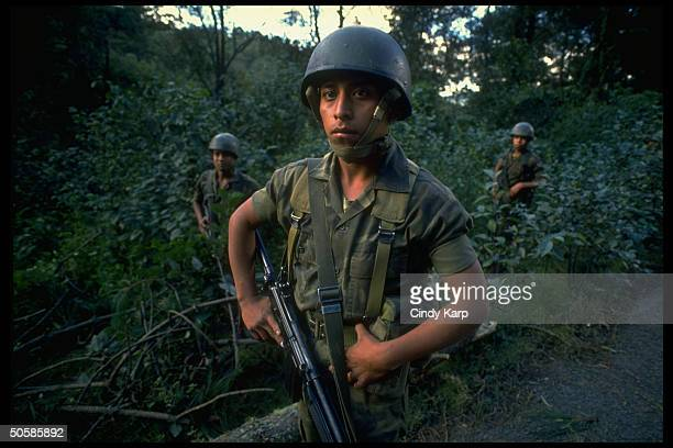 Guatemalan soldiers at ready stalking through foresty area on alert for guerrilla attempts to sabotage pres runoff elections