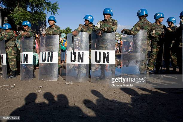 """""""Guatemalan soldiers with riot gear who are part of MINUSTAH provide security as hundreds of hungry people queue for food relief in the flooded city..."""