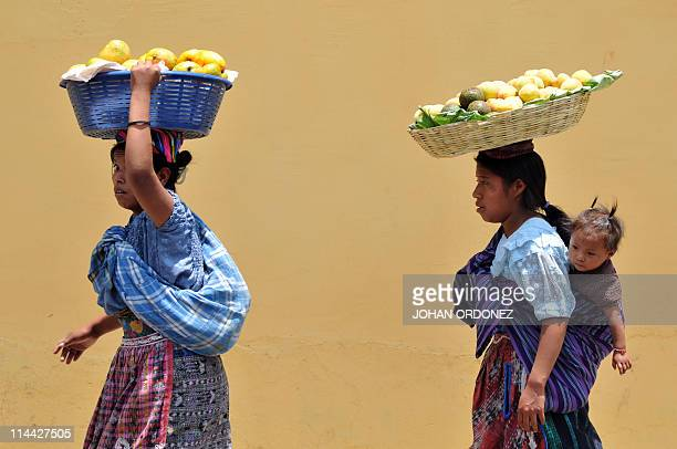 Guatemalan women walk by in Antigua Guatemala on May 19 2011 near the place where the presidents of Guatemala Honduras and Salvador meet to discuss...