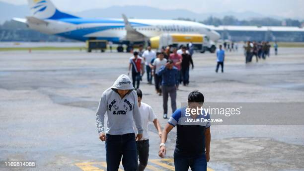Guatemalans walk off a plane during the arrival of a flight coming from Mesa, Arizona with deported Guatemalan Citizens at La Aurora International...