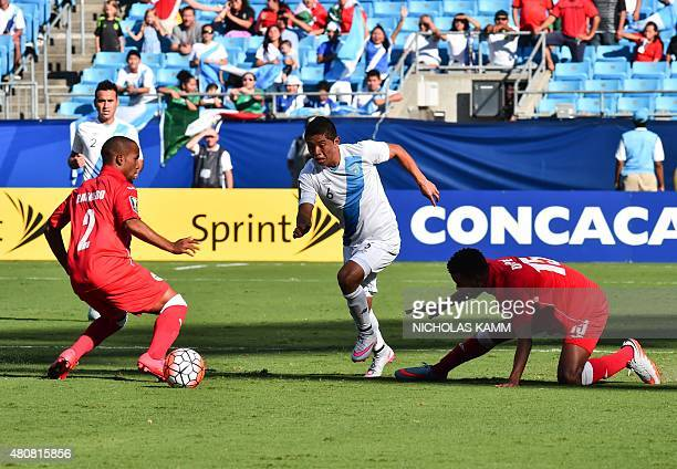 Guatemala's Carlos Mejia gets past Cuba's Andy Vaquero and Adrian Diz Pe during the CONCACAF Gold Cup Group C match in Charlotte North Carolina on...