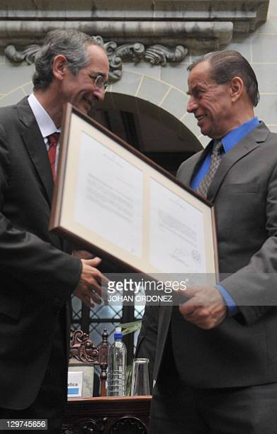 Guatemala's President Alvaro Colom hands on a framed letter of apology to the son of former president Jacobo Arbenz Jacobo Arbenz Vilanova on October...