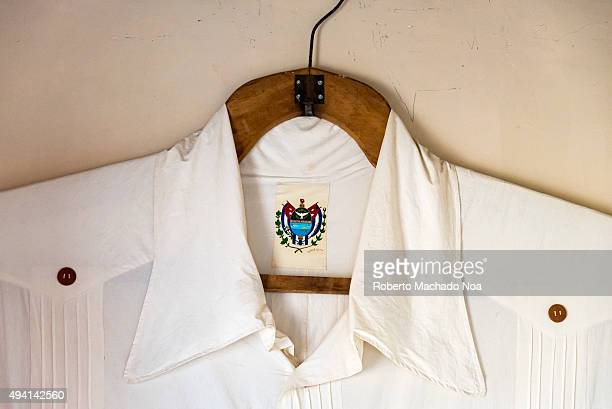 Guayabera or garment on display at the Guayabera Museum, Sancti Spiritus, Cuba. Close up of white shirt with the 'shield of the city of Sancti...