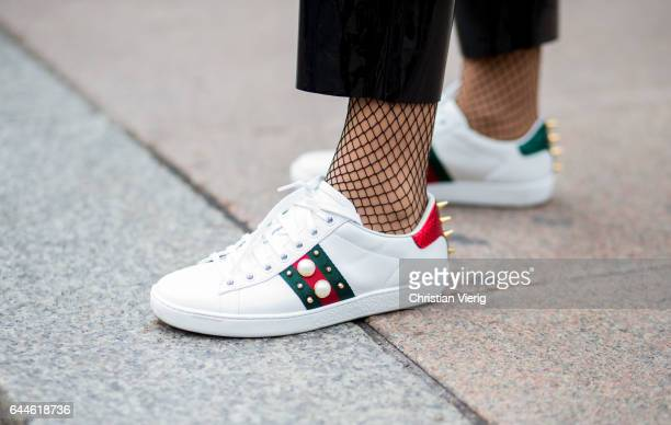 Gucci sneaker and fishnet tights outside Fendi during Milan Fashion Week Fall/Winter 2017/18 on February 23 2017 in Milan Italy