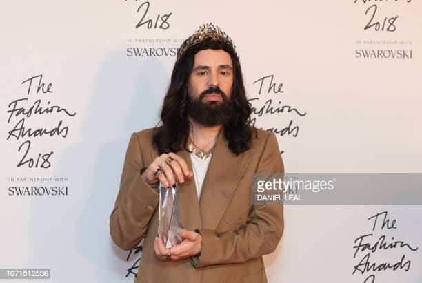 Gucci's Italian fashion designer Alessandro Michele poses with the Brand of the Year award during the British Fashion Awards 2018 in London on...