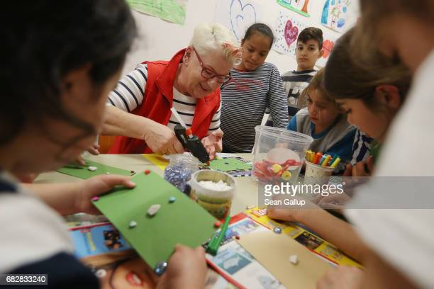 Gudrun Sziede a local volunteer leads children in arts and crafts at the playroom at the shelter for refugees and migrants where the children live in...