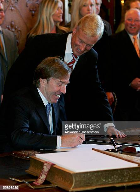 """Guenther Netzer signs the """"Golden Book of Hamburg"""" with Major Ole van Beust during the reception of the Senate of Hamburg at City Hall October 11,..."""