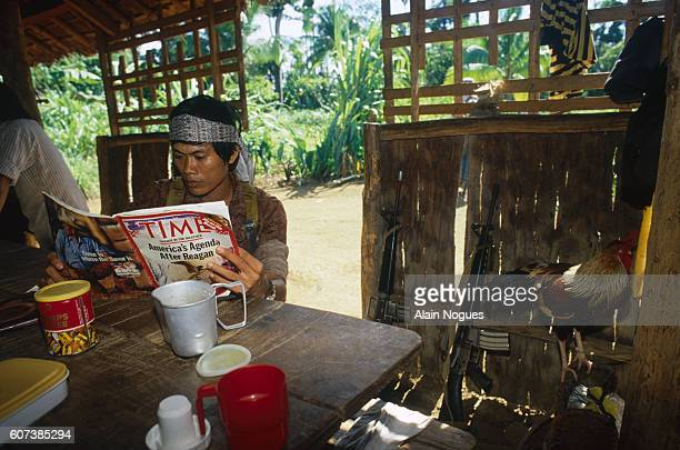 A guerilla fighter reads Time Magazine the title of which reads 'America's Agenda After Reagan' under a wooden shelter at the New People's Army...