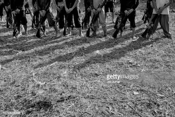 NPA guerilla fighters march in formation inside a stronghold on December 12 2018 in a remote village in the Bicol region Philippines Backed by a...