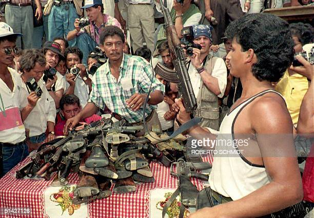 A guerilla member from the Ejercito de Liberacion Nacional turns in his weapon 09 April 1994 in Flor del Monte Colombia to government authorities...