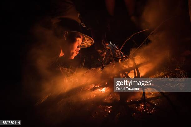 A guerilla of the New People's Army blow embers into a fire to keep warm on April 1 2017 in the remote hinterlands of Mountain Province Philippines...