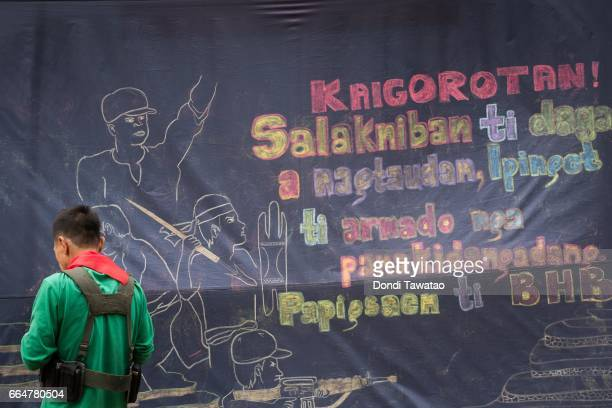 A guerilla of the New People's Army stand before a streamer enjoining rural and indegenous folk to join the NPA on April 1 2017 in the remote...