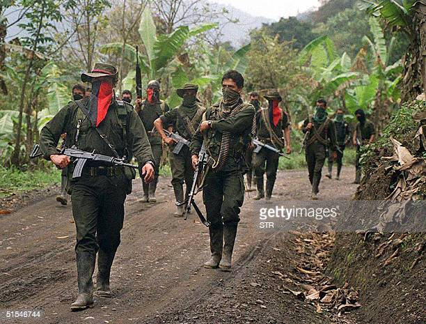 Guerilla soldiers of the National Liberation patroll a secondary streen in Sarare 27 February 2000 in the Department of Arauca Guerrileros del...