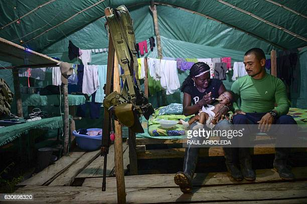 TOPSHOT FARC guerillas members Vanesa Cortez feedsher daughter Manuela next to Victor Gutierrez at their camp front 34 Alberto Martinez just days...