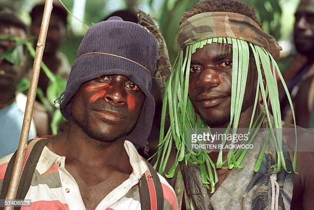 Guerillas of the Bougainville Revolutionary Army some still wearing camouflage watch the signing ceremony of the Bougainville Ceasefire Agreement at...