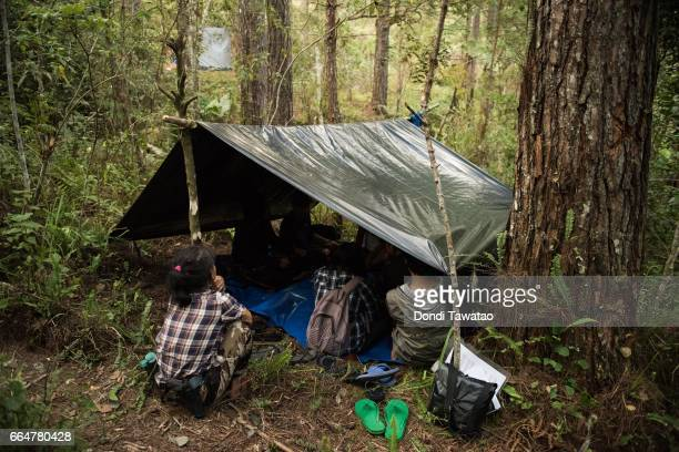 Guerillas of the New People's Army huddle inside a tent amid trees and dense vegetation on April 1 2017 in the remote hinterlands of Mountain...