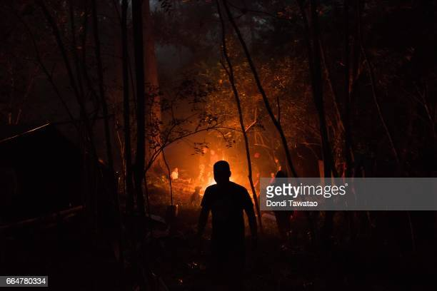 Guerillas of the New People's Army huddle near a fire to keep warm on April 1 2017 in the remote hinterlands of Mountain Province Philippines The NPA...