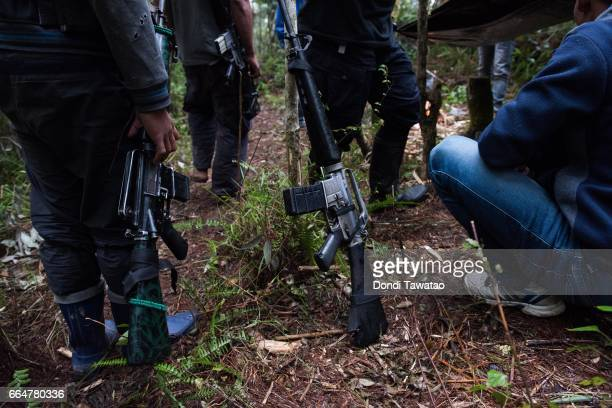 Guerillas of the New People's Army huddle together near a forward tent on April 1 2017 in the remote hinterlands of Mountain Province Philippines The...